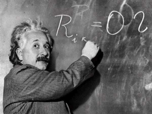 Albert Einstein writes an equation on a chalkboard