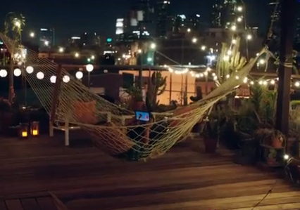 Amazon TV ad shows Kindle in a hammock on a city deck