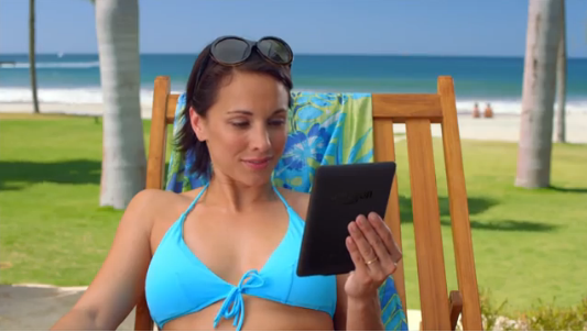 Anna Zielinski in a blue bikini reading a Kindle at the beach in Amazon Paperwhite TV ad